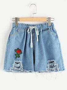 Shorts roto en denim aplique de flor de borde crudo